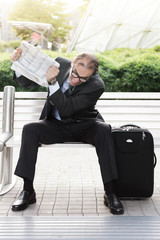 Angry businessman with newspaper in his hands