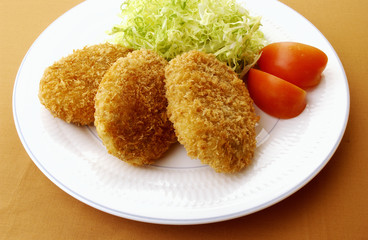 Plate of fried croquettes, colored background