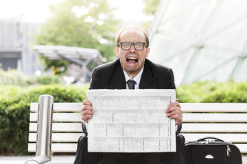 screaming businessman with newspaper in his hands