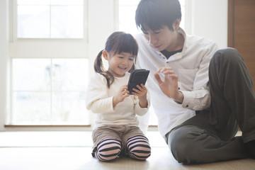 スマートフォンで遊ぶ親子