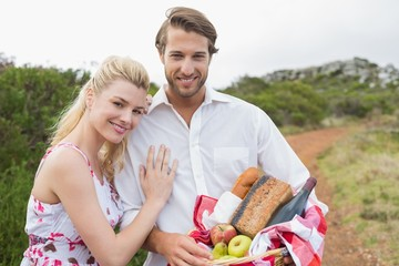 Cute couple going for a picnic smiling at camera