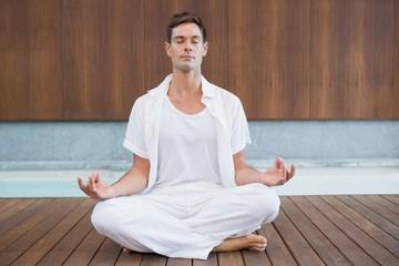 Handsome man in white meditating in lotus pose