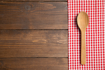 Spoon on wooden table with red checked tablecloth