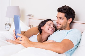 Attractive couple lying in bed with tablet pc