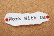 The phrase Work With Us on a cork notice board