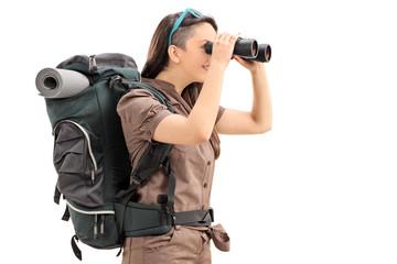 Female hiker looking through binoculars