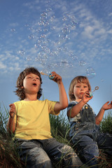 two happy boy blowing bubbles on nature