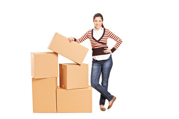 Happy woman standing by a bunch of boxes