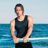 Young handsome man portrait at the sea with surfboard. Filtered