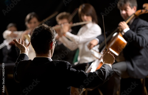 Conductor directing symphony orchestra - 66334009