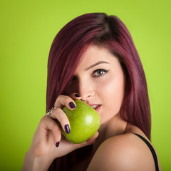 Redhead woman portrait with apple against colorful green backgro