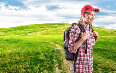 Happy female traveler with backpack walking in countryside