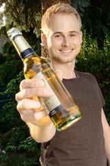 Junger Mann trinkt Bier auf Gartenfest