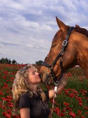 Junge Frau mit Pferd im Rapsfeld