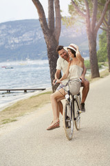 man carrying his woman on a bike in the lake zone