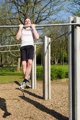 junger mann übt sich an klimmzüge