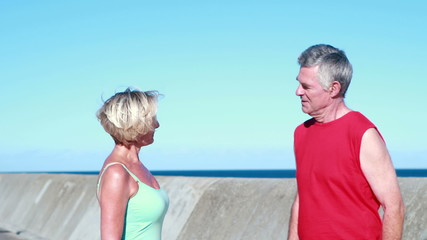 Fit senior couple chatting on a break from their run