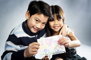"""Little asian boy and girl  holding picture wiith word """"I love mo"""