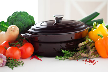 Cast iron pot and fresh vegetables on the table, selective focus