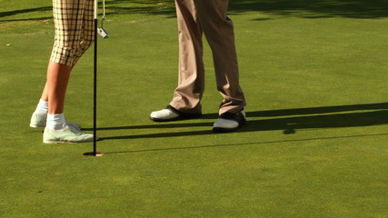 Couple standing on the putting green of golf course