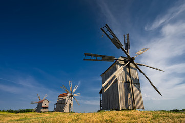 Three traditional windmills on the countryside at sunset