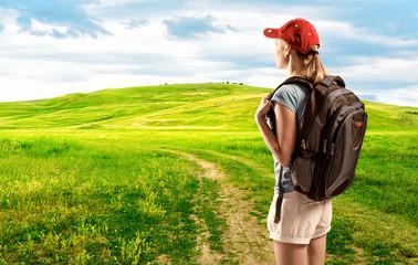 Woman hiker standing on path through green hills