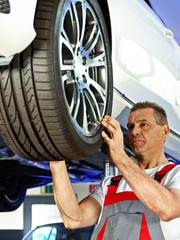Car mechanic looking at the tread pattern of a tire