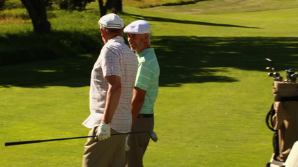 Two male friends chatting and walking on the golf course past th