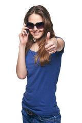 Smiling woman gesturing thumb up while talking on cell phone
