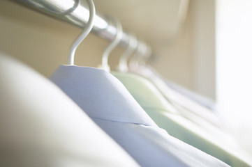Pastel shirts hanging in a closet