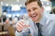 Smiling young man drinking water in restaurant