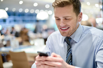 Happy young executive using smart phone