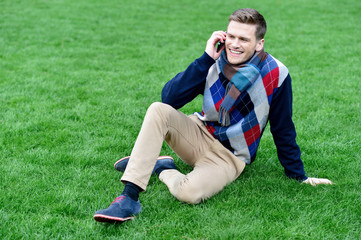 Relaxed young fashion guy on call