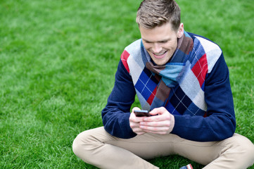 Cheerful young relaxed guy using mobile phone