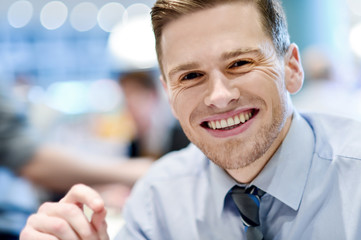 Smiling relaxed young man in restaurant
