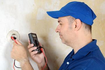 Elektriker misst Strom an Steckdose
