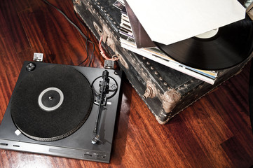 Turntable on floor and old vinyl records on a trunk