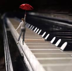 woman jumps with umbrella on a piano keyboard