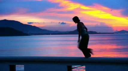 Happy Woman Jumping in Sea Sunset on Samui island