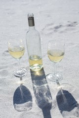 White wine bottle and glasses on the sand