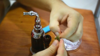 laying of marijuana in a hookah smoking and smoke deflation.