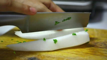 Cutting of garden radish for salad on wooden board.