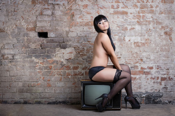 Young sexy woman with retro TV