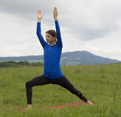 Man in Warrior Pose during yoga outdoors in nature