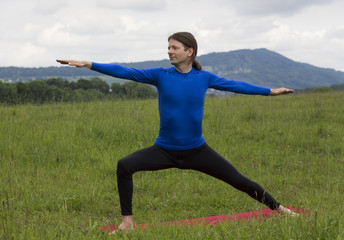 Man in Warrior II Pose during yoga outdoors