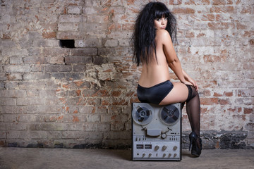 Sexy nude woman sitting on retro tape against the brick wall.