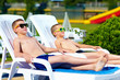teenage boys relaxing on chaise-longue in waterpark