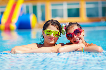 happy girl friends enjoy swimming in the pool