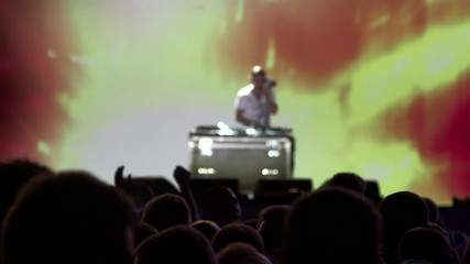 Dj mixing records on illuminated stage at concert