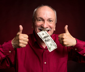 Elderly man holding dollar bill in the mouth